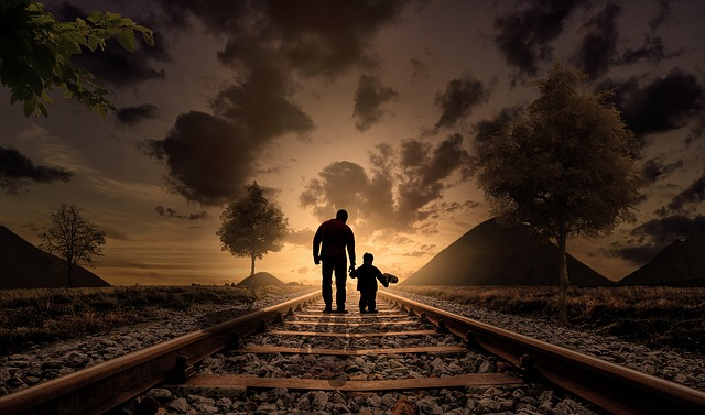 man and a child on a railroad at sunset