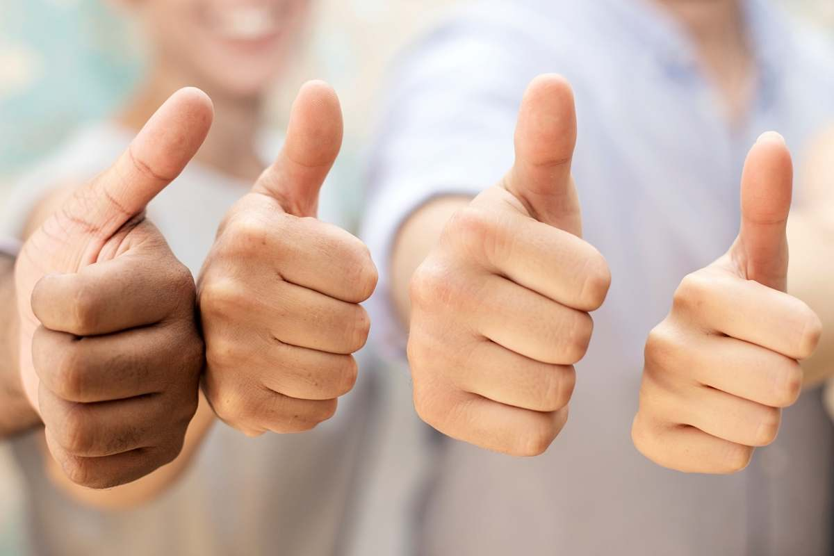 four people giving a thumbs up